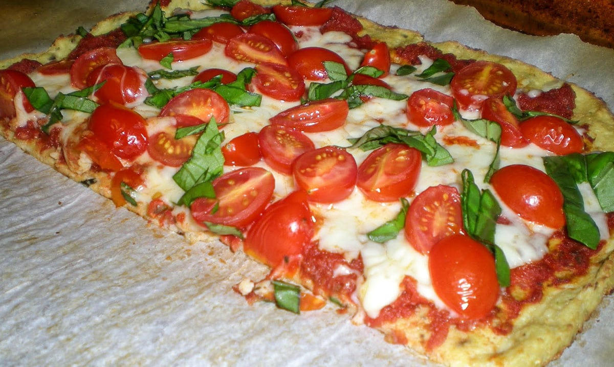 cauliflower crust pizza with tomatoes and basil