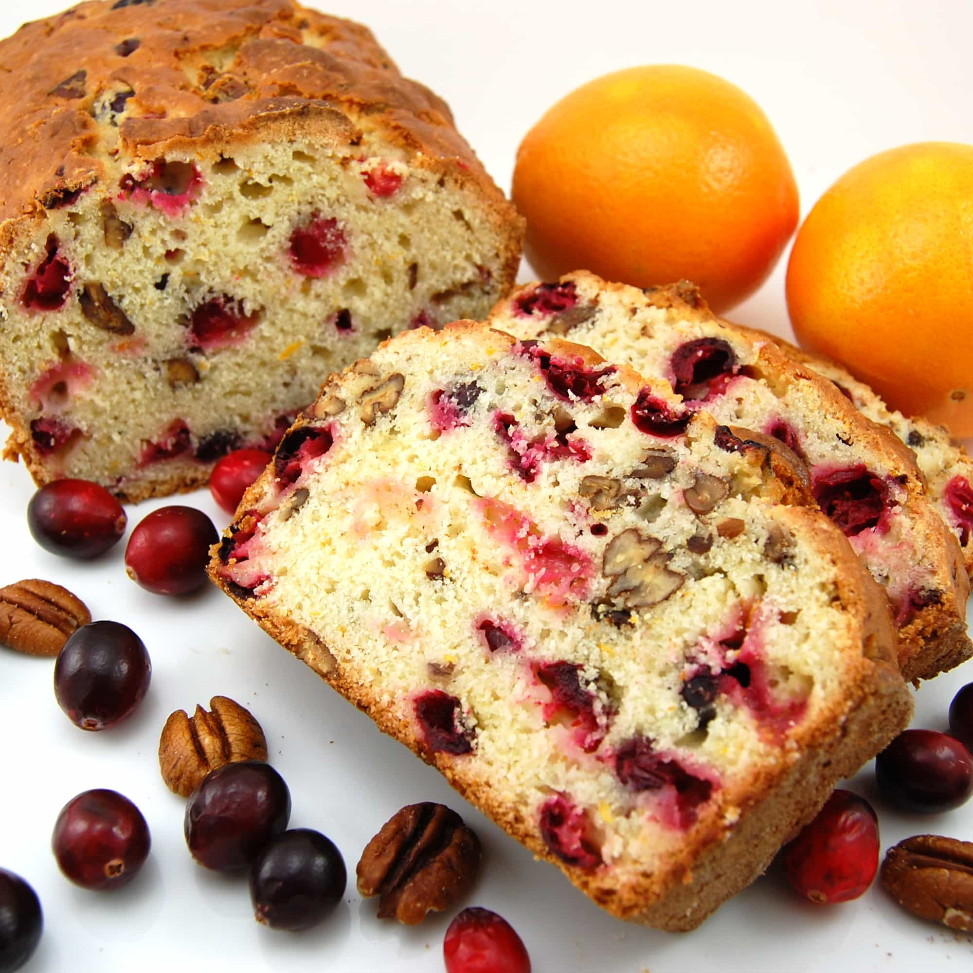 bread on a platter with fresh cranberries and oranges along side