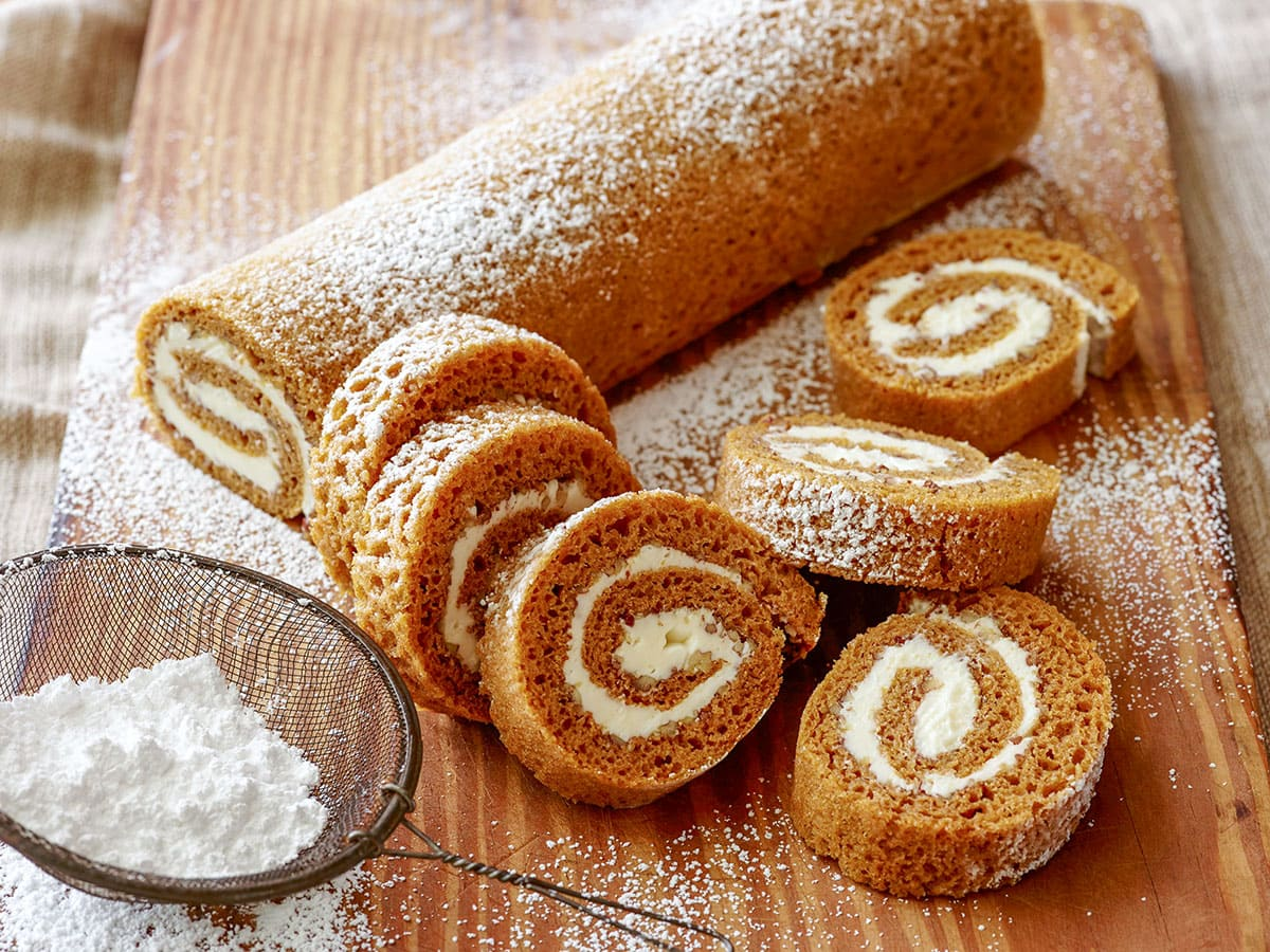 pumpkin roll and sliced pimpkin roll on a cutting board next to a bowl of powdered sugar