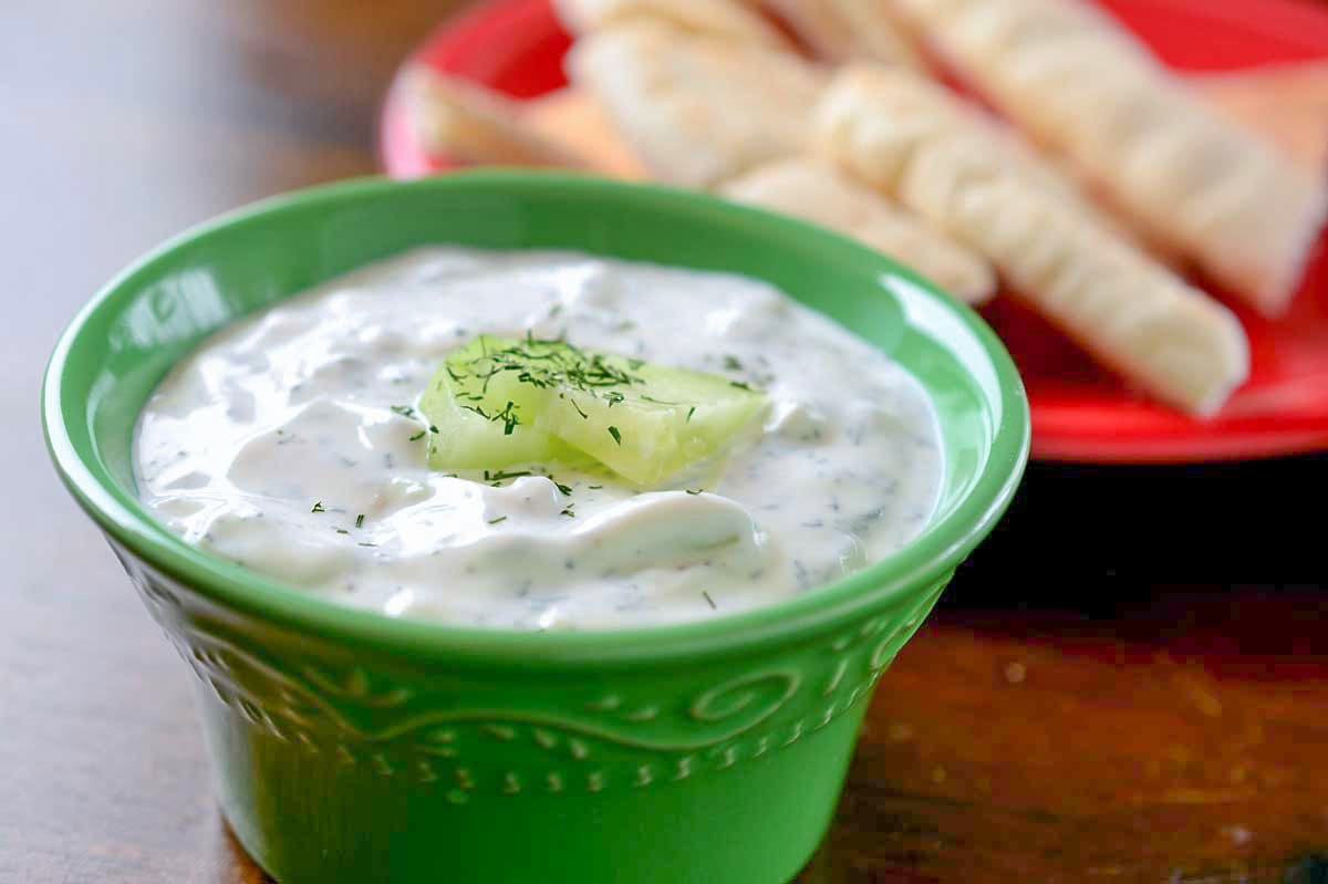 bowl of tzatziki and a plate with slices of pita bread behind it.